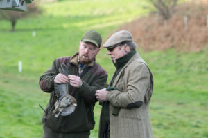 Beater and member examining partridge